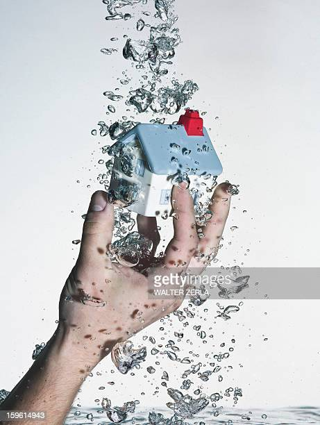 Hand grasping model house in water