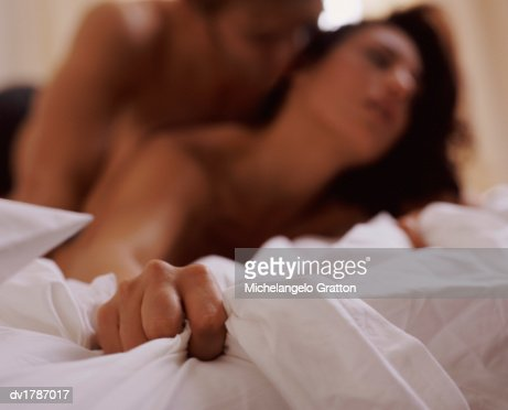Hand Gripping Sheets, Couple Naked on Bed in Background : Stock Photo