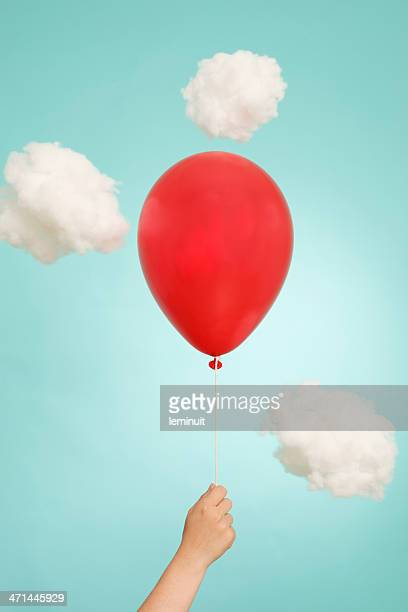 Hand, helium red balloon and clouds