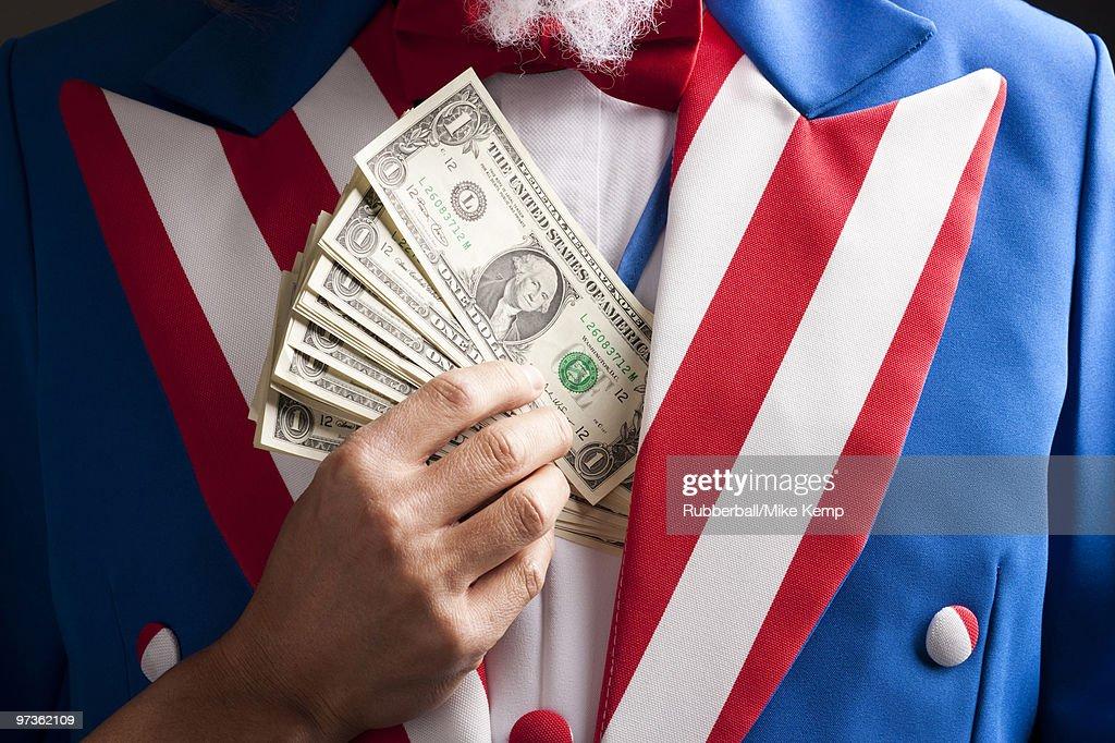 Hand hiding banknotes under vest, studio shot