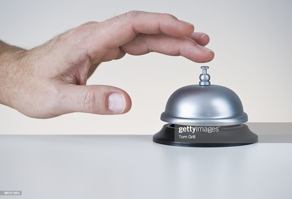 Hand hitting a desk bell : Stock Photo