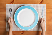 Hand hold fork and knife with and empty plate on brown wood background