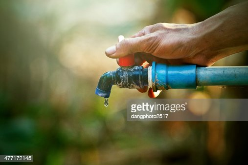 hand hold outdoor water tap with tube : Stock Photo