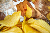 Hand hold potato chips inside snack foil bag