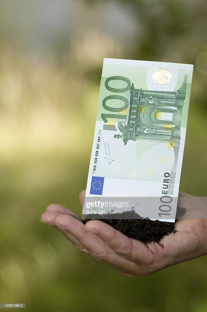 Hand holding 100 Euro bill in soil