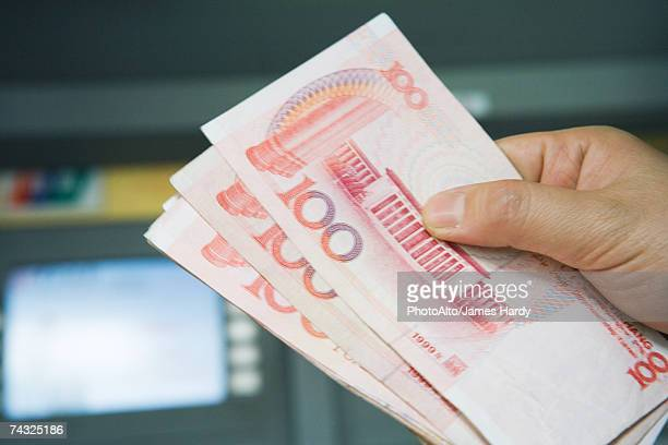 Hand holding 100 Yuan bills