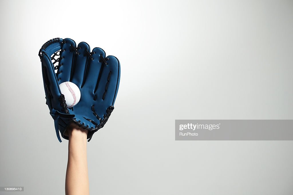 Hand holding a baseball glove and ball