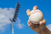 Hand holding a baseball on high pole Spotlight Stadium lights with blue sky background.