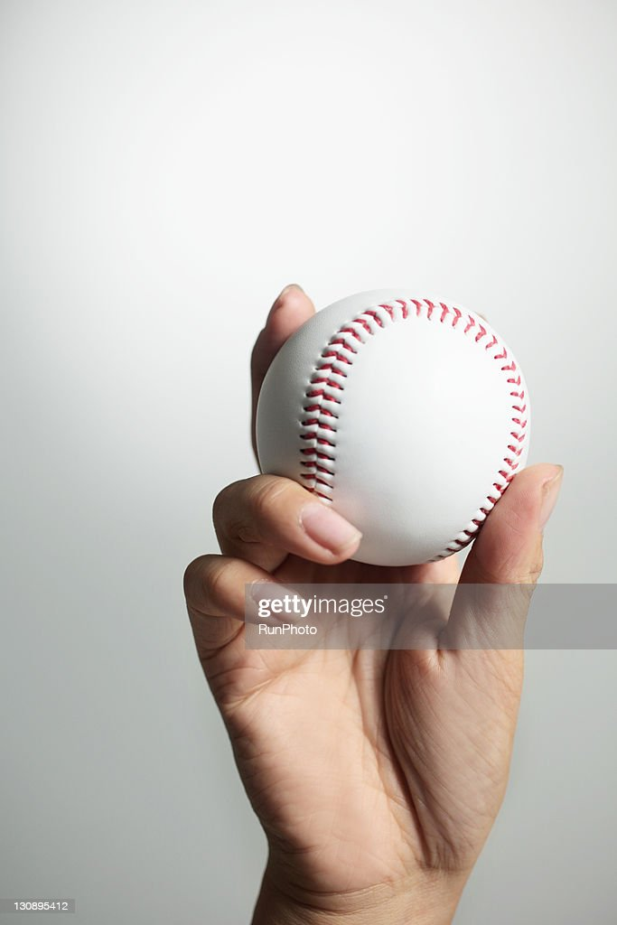 Hand holding a baseball,hands close-up : Stock Photo