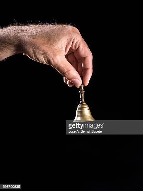 Hand holding a bell of bronze on black background
