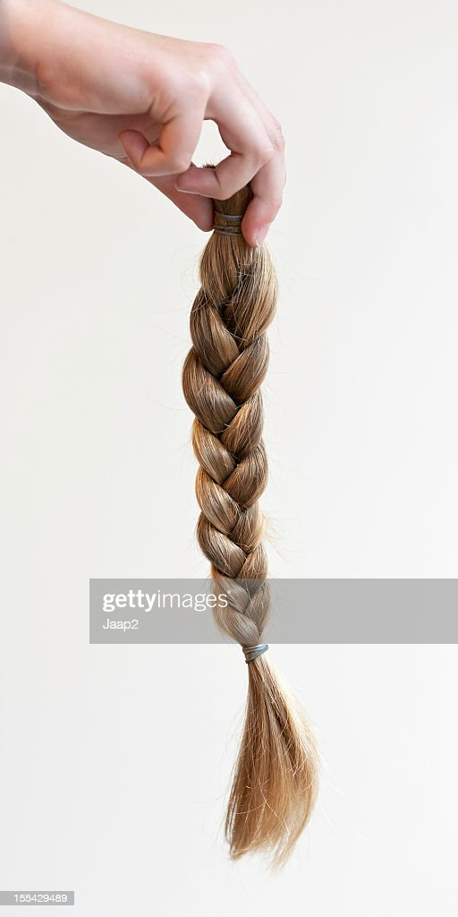 Hand holding a braided ponytail cut off for making wig : Stock Photo