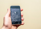 Hand holding a broken smart phone