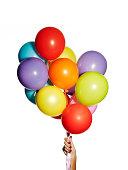 Hand hält einen Haufen bunte Ballons
