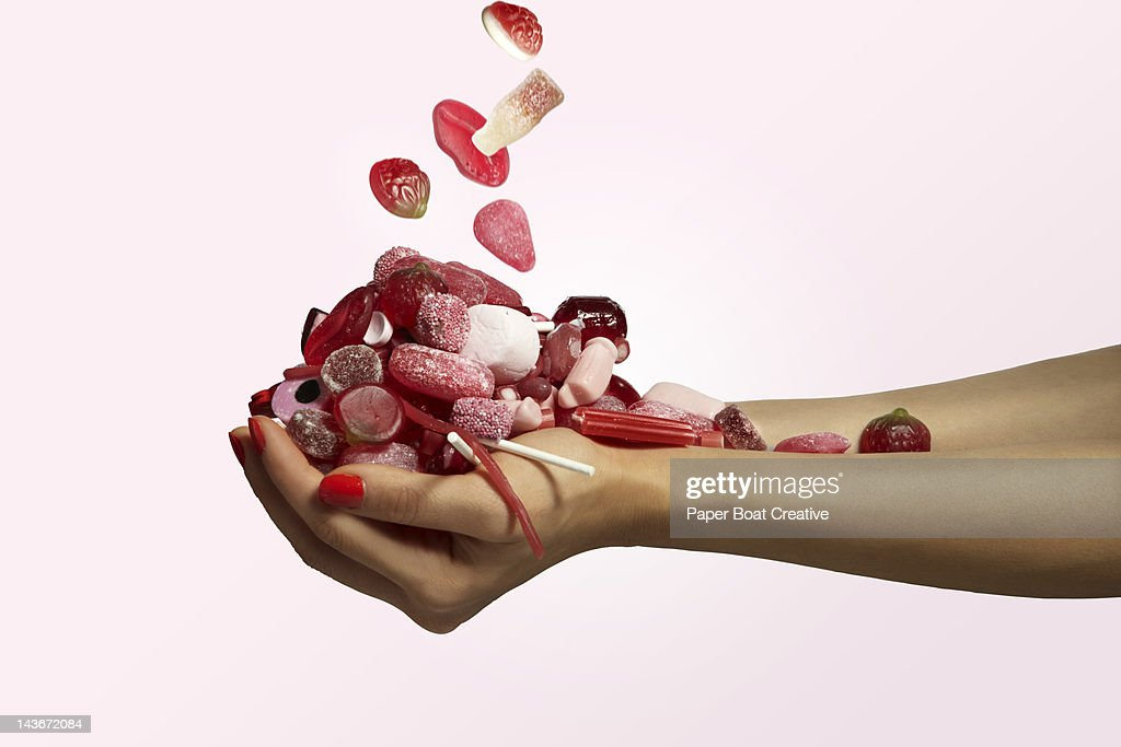 hand holding a bunch of red candy falling