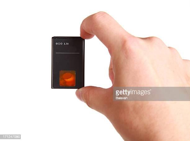 Mano sosteniendo un teléfono móvil sobre fondo blanco de batería