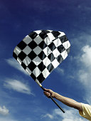 Hand holding a checkered flag