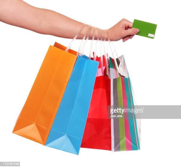 A hand holding a credit card with paper bags