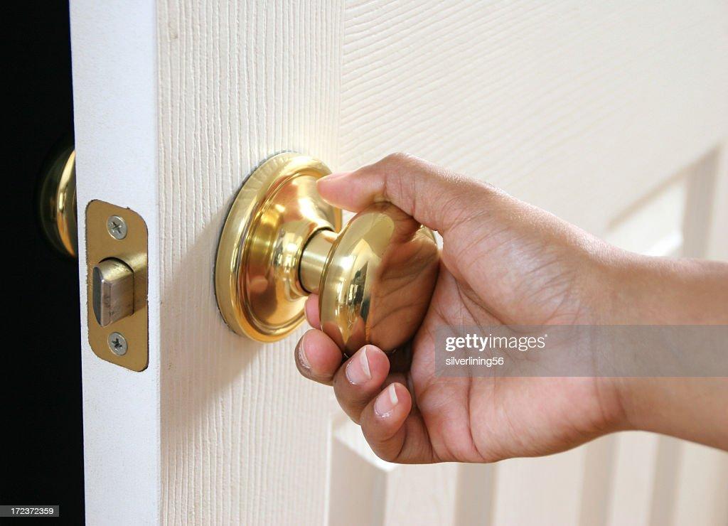 Hand holding a door knob opening a white door : Stock Photo