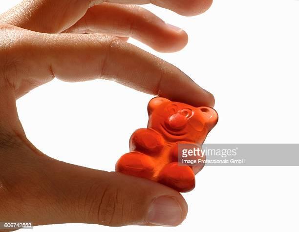Hand holding a gummi bear