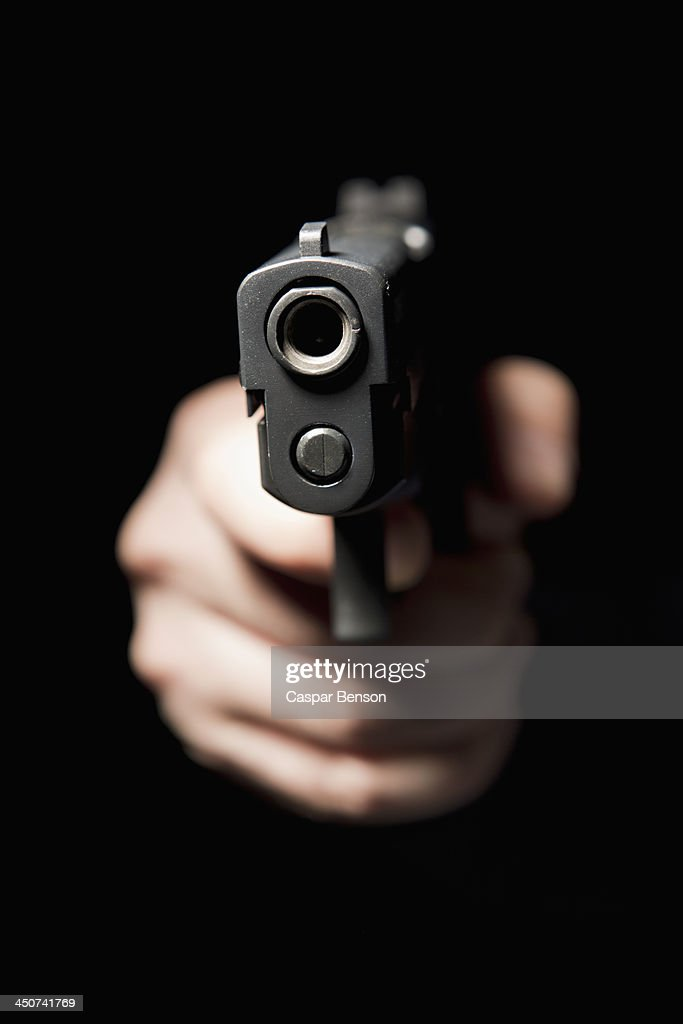 A hand holding a gun and pointing it at the camera, black background