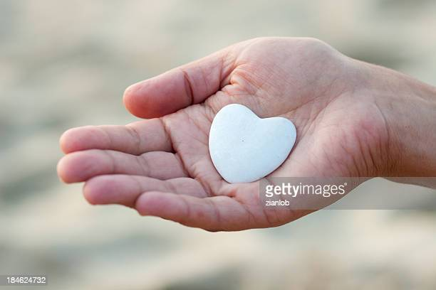 Hand holding a heart shaped stone