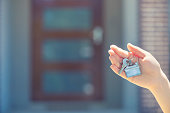 Hand holding a house key in front of a large house. The key ring has a house shaped icon on the end and is shiny silver colour. You can see the front door in the background. The key ring house icon is