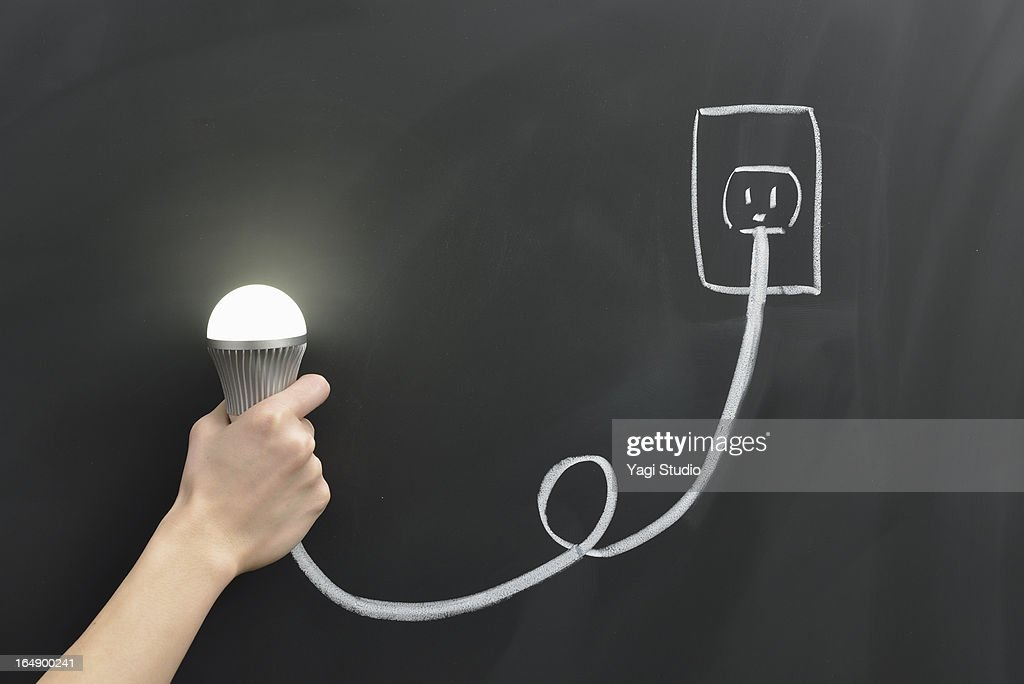 Hand holding a light bulb and the outlet : Stock Photo