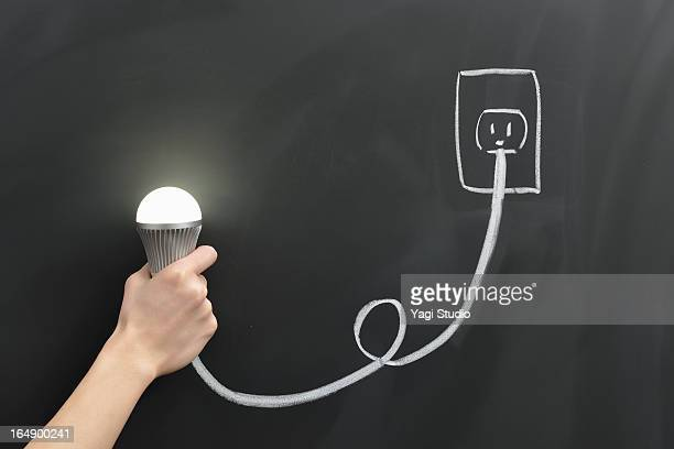 Hand holding a light bulb and the outlet