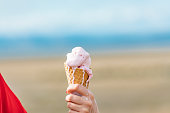 Hand holding a melting strawberry Ice-Cream Cone, Morecambe Bay, Lancashire on a sunny July late afternoon day.
