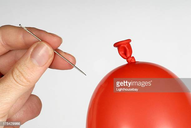 Hand holding a needle about to pop a red balloon