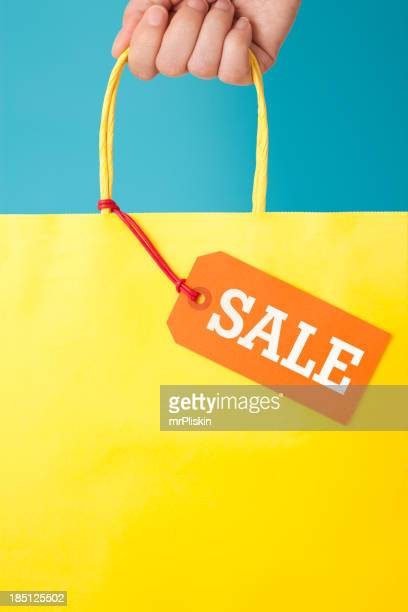 A hand holding a paper bag with a sale tag