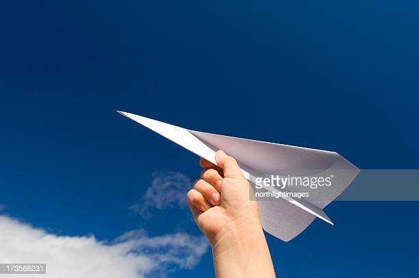 A hand holding a paper plane with the view of the sky
