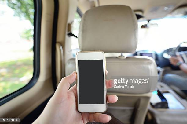 Hand holding a phone in the back seat of a van