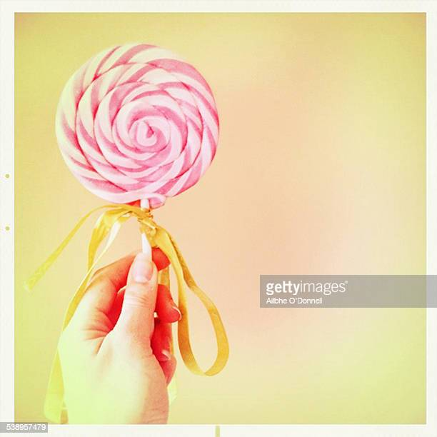 Hand holding a pink and white striped lollipop