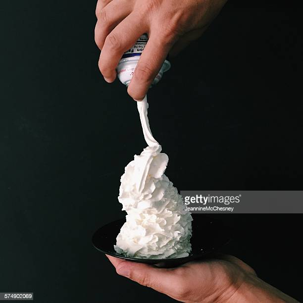 Hand holding a plate with whipped cream