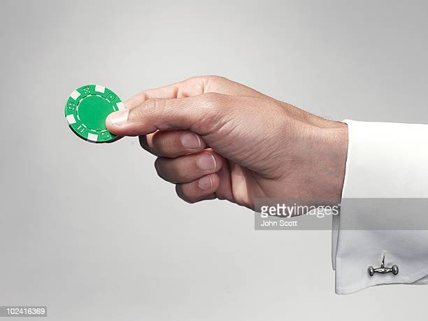 Hand holding a poker chip