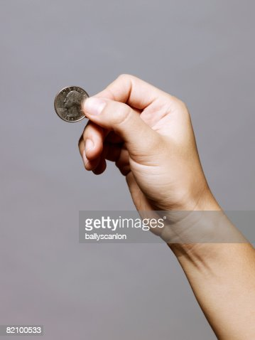 hand holding a quarter (25 cents) : Stock Photo