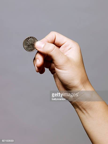 hand holding a quarter (25 cents)