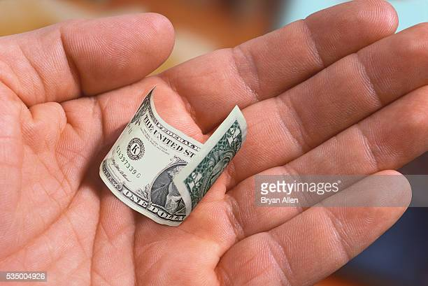 Hand Holding a Shrunken Dollar Bill