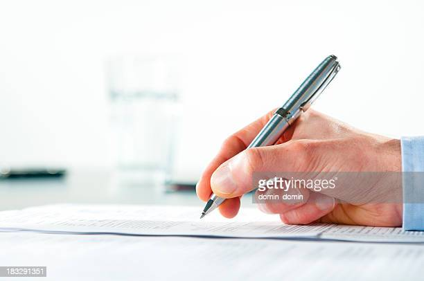 Hand holding a silver pen and signing a document