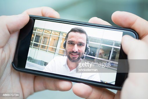 hand holding a smart phone during a skype video : Stock Photo