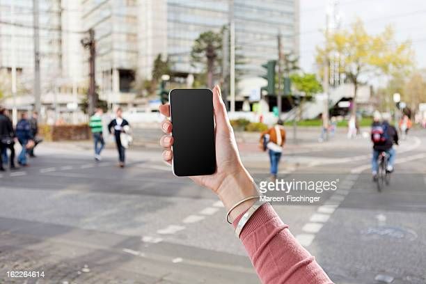 Hand holding a smart phone in an urban area