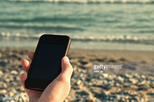 Hand holding a smartphone on a pebble beach