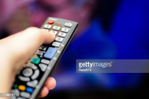 Hand holding a television remote control  : Stock Photo