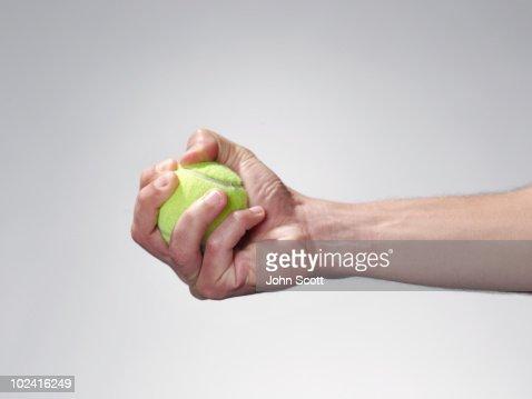 Hand holding a tennis ball