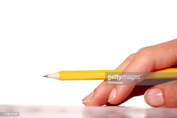 Hand holding a yellow pencil raised from a table