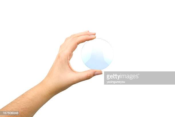 Hand holding an eyeglass lens without the glasses on white