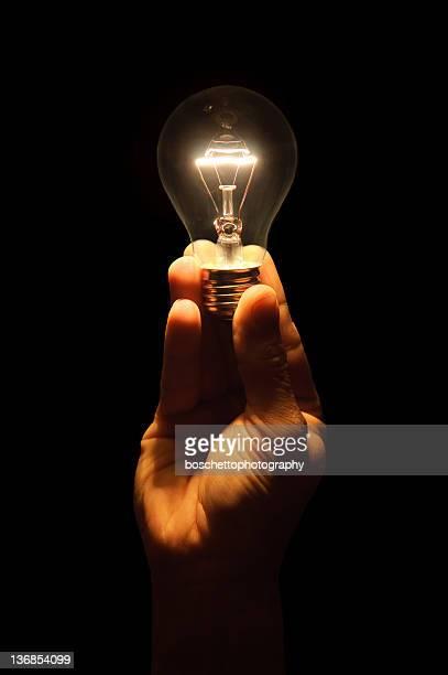 Hand holding an incandescent light bulb.