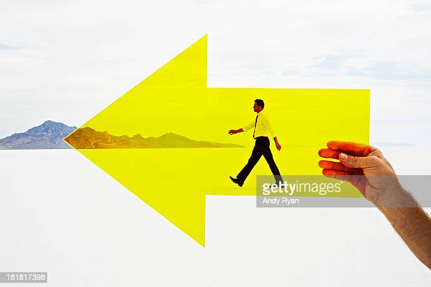 Hand holding arrow with man walking in background.