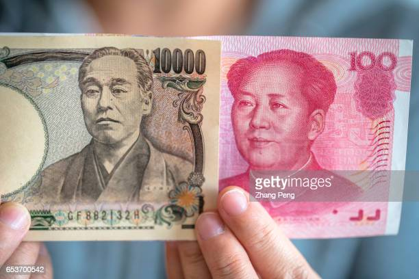 Hand holding banknotes of a onehundred RMB banknote and a tenthousand Yen banknote arranged for photography Rises in the yuan/yen exchange rate...